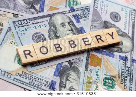 The Word Robbery On Dollar Usa Background. Theft And Stealing Money Concept.