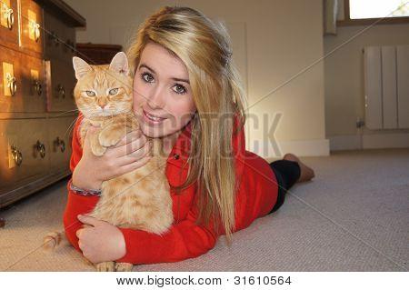 Girl cuddling her ginger cat