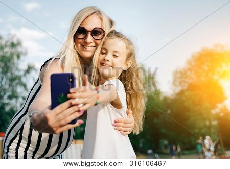 Image Of Happy Mother And Daughter Taking Selfie On Street On Summer Day In Park. Lensflare Effect