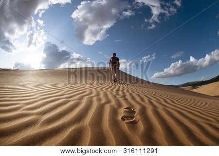 One Lonely Man Walks In Desert On Dunes