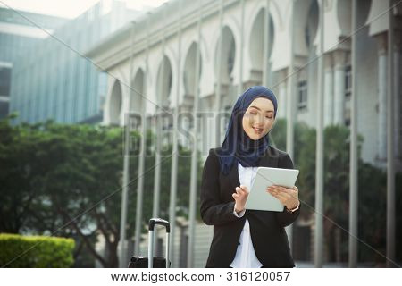Muslim woman working on table pc outdoor, business travel concept.