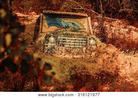 Off-road Vehicle Goes On The Mountain. Mudding Is Off-roading Through An Area Of Wet Mud Or Clay. Tr