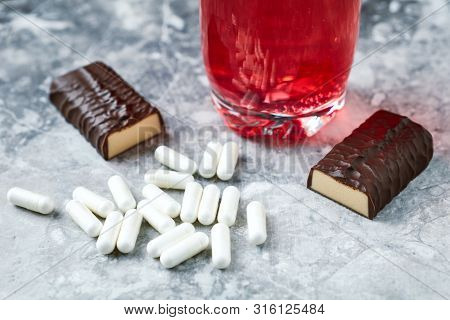 Arginine Capsules, High Protein Bar And Bcaa Drink. Bodybuilding Food Supplements On Bright Stone Ba