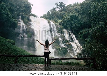 Beautiful Woman Looking At Big Waterfall After Hiking In Chiang Mai (thailand) Arms Spread With Copy