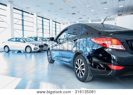 New Cars In A Car Showroom. Close View Of Black Sedan