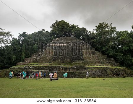 LAMANAI, BELIZE-JANUARY 15, 2018: Tourists observe and photograph the Mayan temple of Lamanai in Belize.