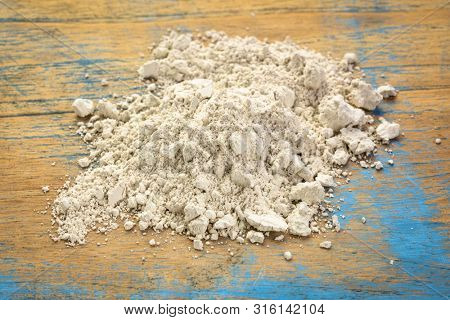 food grade diatomaceous earth supplement - small pile of powder on a grunge wood