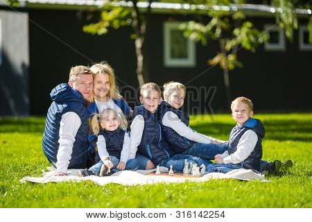 Big Family Relaxing In Green Nature. Happy Family Portrait On Outdoor, Group Six People Sit On Grass