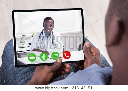 An African Man Doing Video Conference With Doctor On Digital Tablet