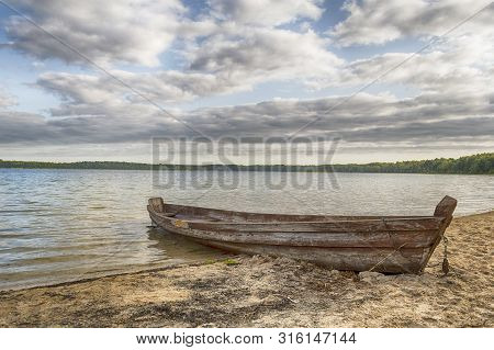 The Last Pier Of The Boat. Waves Of Clear Water Crashing Into The Side Of An Old Broken Boat Abandon
