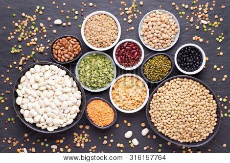 Legumes, lentils, chickpeas and beans assortment in different bowls on black stone background, top view