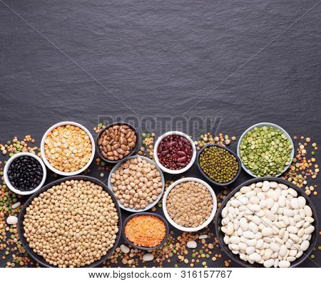 Legumes, lentils, chickpeas and beans assortment in different bowls on black stone background, top view with copy space
