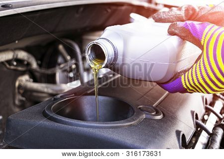 Change The Oil. Hand Mechanic In Repairing Car. Close Up Oil For Car Engine. Motor Oil Pouring To Ca
