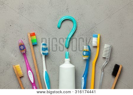 Toothpaste In The Form Of A Question Mark And Many Different And Colored Toothbrushes. Concept Of Ho