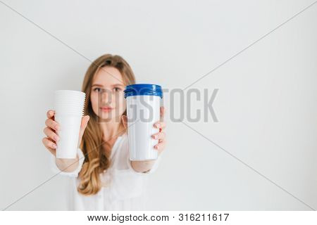 Girl Holding A Useful Reusable Glass And Disposable Plastic Cups For Comparison