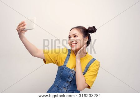 Young Asian Woman Wearing A Jeans Dungaree Who Taking Selfie And Smiling