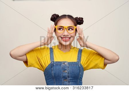 Beautiful Asian Woman Has Two Buns Of Hair Wearing A Jeans Dungaree And Adjusting Glasses