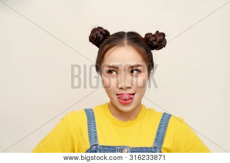 Beautiful Young Asian Girl Wearing Jeans Dungaree With Two Buns Hair On White Background