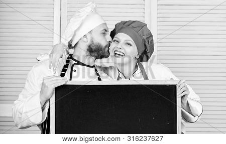 Man And Woman Chef Cooking Food Together. Couple With Blackboard For Advertisement. Lovely Family At