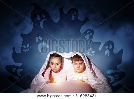 Scared Children In Pajamas With Flashlights Hiding Under Blanket. Frightened Kids Sitting In Bed. Ch