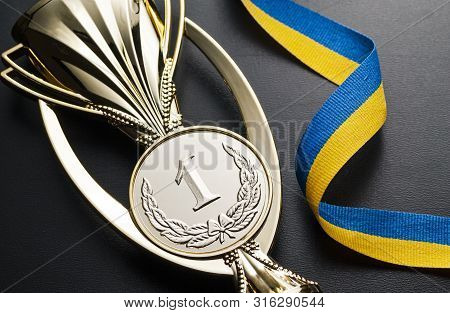 Gold Winners Medal For A Competition, Championship Or Race With A Twirled Blue And Yellow Ribbon On
