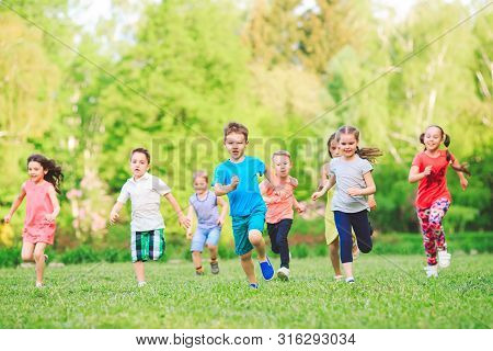 Many Different Kids, Boys And Girls Running In The Park On Sunny Summer Day In Casual Clothes.