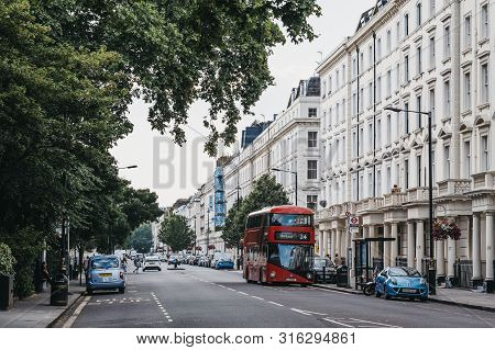 London, Uk - July 16, 2019: Red Double Decker Bus Driving Past A Row Of White Terraced Houses On A S