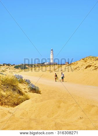Barbate, Spain - June 26, 2019. Tourists Walking In A Broad Beach Of Fine Sand Dunes Of The Cabo De