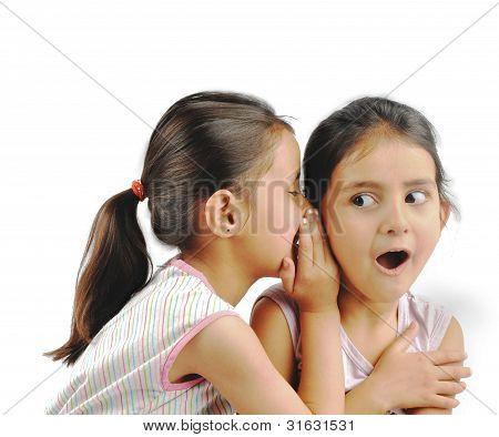 Naughty girl whispering in her friend's ear.