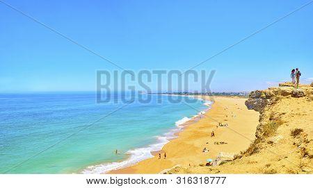 Barbate, Spain - June 26, 2019. Tourists Watching To The Faro De Trafalgar Beach, A Broad Beach Of T