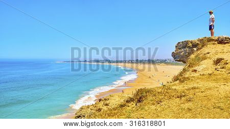 A Tourist Watching To The Faro De Trafalgar Beach, A Broad Beach Of The Cabo De Trafalgar Cape Natur
