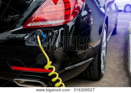 Ev Car Or Electric Car At Charging Station With The Power Cable Supply Plugged In, Charging Hybrid C