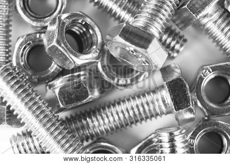 Metal Bolts And Nuts  In A Row Background. Chromed Screw Bolts And Nuts Isolated. Steel Bolts And Nu