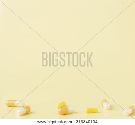 A Few White-yellow Drug Capsules On The Yellow Background