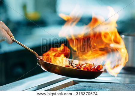 Modern Kitchen. Cooks Prepare Meals On The Stove In The Kitchen Of The Restaurant Or Hotel. The Fire