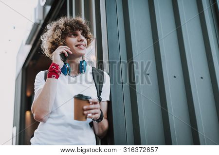 Mirthful Man Talking On The Phone And Smiling
