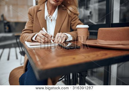 Lady Writing In Notebook Outdoors Stock Photo