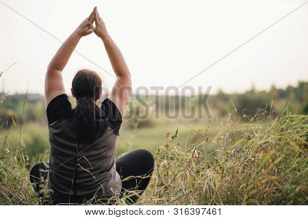 Body Positive, Yoga, Meditation, Tranquility, Relax. Overweight Woman Meditating Sitting In The Mead