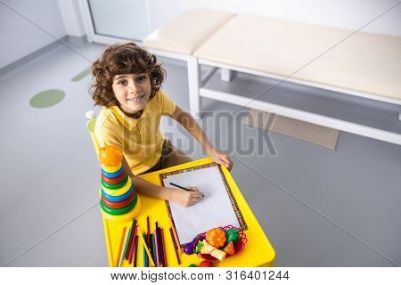 Happy Boy Waiting For Doctor In Playroom Stock Photo