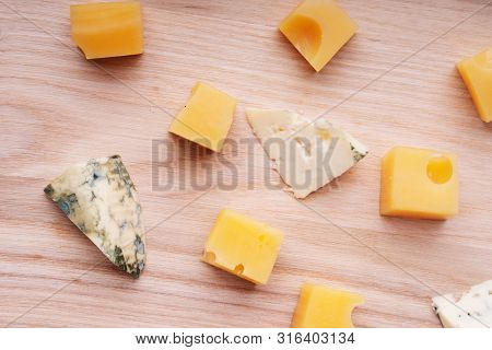Pieces Of Cheddar Cheese And Blue Roquefort On A Cutting Board.