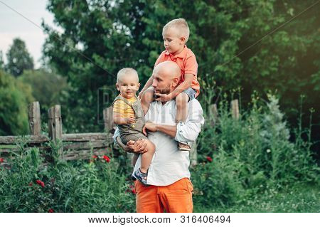 Caucasian father hugging playing with sons boys in park on summer day. Dad holding carrying children kids. Authentic lifestyle touching tender moment. Family life happy fatherhood concept. poster