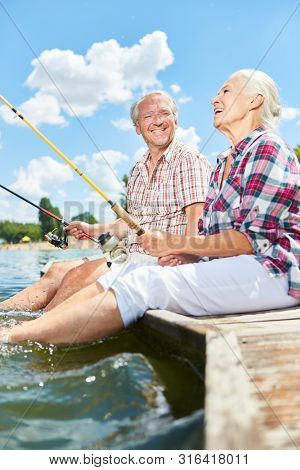 Happy seniors couple is having fun together while fishing by the lake in summer