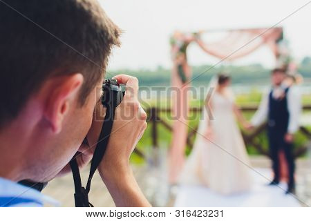 Wedding Photographer Takes Pictures Of Bride And Groom In City. Wedding Couple On Photo Shoot. Photo