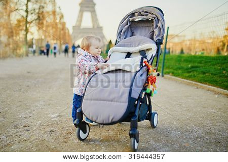 Baby Girl Standing On The Street And Holding On To Pushchair. Little Child Pulling Up Outdoors. Happ