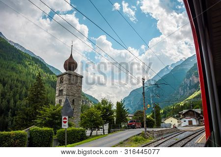 View Of Pfarrkirche St.niklaus With Forest And Mountains On Background From Panoramic Train. Station