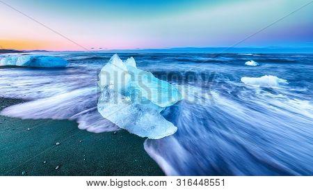 Incredible Pieces Of The Iceberg Sparkle On Famous Diamond Beach At  Jokulsarlon Lagoon During Sunse