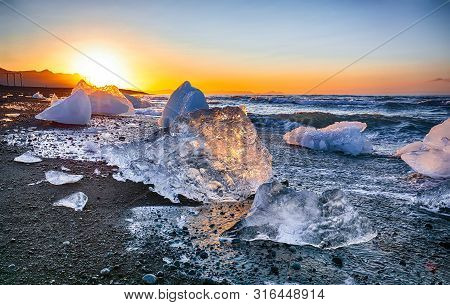 Incredible Pieces Of The Iceberg Sparkle On Famous Diamond Beach At  Jokulsarlon Lagoon During Sunse
