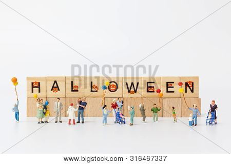 Miniature People:  Happy Family Holding Balloon And Copy Space For Text, Happy Halloween Concept
