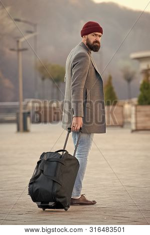 Carry travel bag. Man bearded hipster travel with luggage bag on wheels. Adjust living in new city. Traveler with suitcase arrive airport railway station urban background. Hipster ready enjoy travel. poster