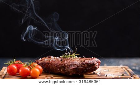 Steakhouse Menu. Striploin Steak. Grilled Beef Meat With Cherry Tomatoes And Burning Rosemary Twig.